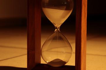 Sand falls on hourglass