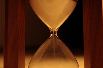 Sand falls down in sandglass closeup