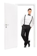 Man in elegant clothes posing by an opened door