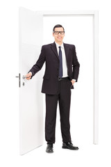 Young businessman posing in front of a door