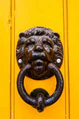 Cast iron door knocker and ring on yellow door