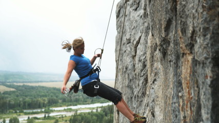 woman repelling down a cliff face