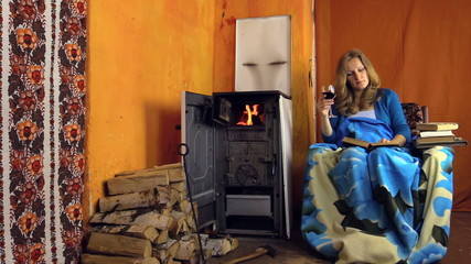 Woman on armchair drink red wine and read book near rural stove