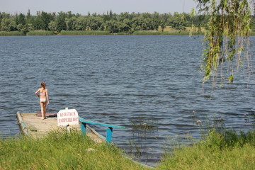 Девочка на старом пирсе у озера