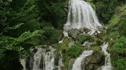 Slow motion/medium shot of waterfall and cliff / St. Beatus Caves, Switzerland