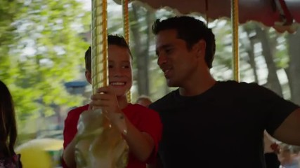 Close up of father and son riding carousel at carnival / American Fork, Utah, United States