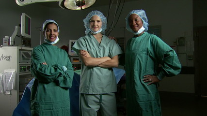 Portrait of a female surgical team in scrubs with arms crossed smiling