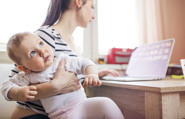 Young mother in home office with computer and her daugher