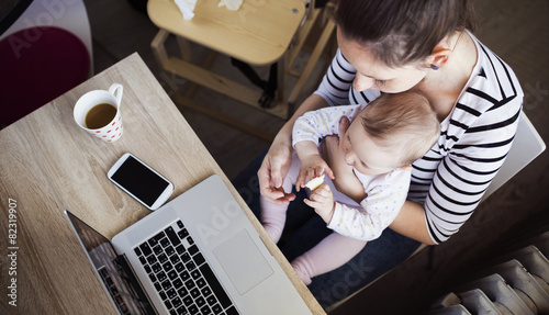 Young mother in home office with computer and her daugher - 82319907