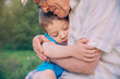 Happy grandson hugging to his grandfather outdoors