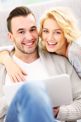 Happy adult couple using laptop at home