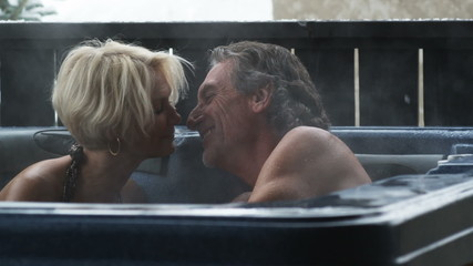 mature couple in a hot tub drinking wine and kissing
