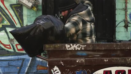 MS Homeless man exiting garbage container, carrying plastic garbage bag, Salt Lake City, Utah, USA