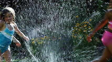 girls running in a sprinkler