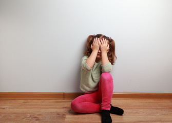 Crying unhappy kid girl sitting on the floor with closed face