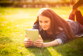 Beautiful girl with tablet or ebook outdoor laying on field