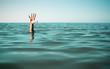 Leinwanddruck Bild - Hand in sea water asking for help. Failure and rescue concept.