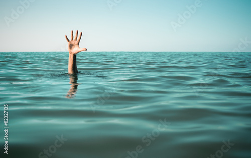 Leinwanddruck Bild Hand in sea water asking for help. Failure and rescue concept.