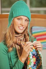 Happy young woman knitting crochet