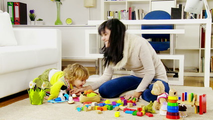 woman with baby daughter playing at home