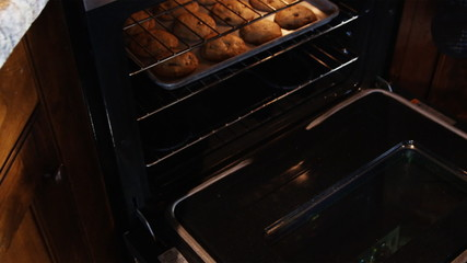 pulling cookies out of the oven