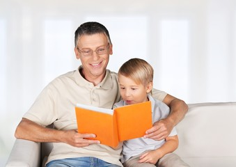 Grandchild. Grandmother and little boy reading book happy