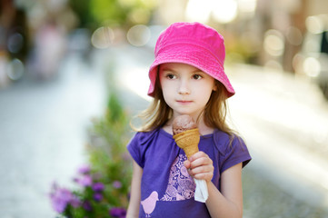 Adorable little girl eating ice-cream outdoors