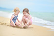 Leinwanddruck Bild - Two little sisters having fun on a beach