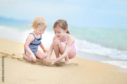 Leinwanddruck Bild Two little sisters having fun on a beach