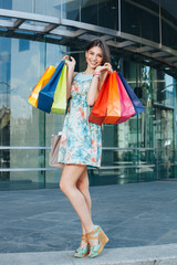 Attractive woman posing with shopping bags in front of the shopp