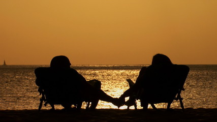 Couple in silhouette sitting in folding chairs on beach at dusk holding hands