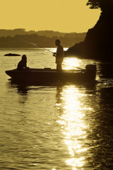 couple fishing with reeds on sea  from recreational boat at suns