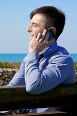 Young businessman on the phone smiling in front of the ocean