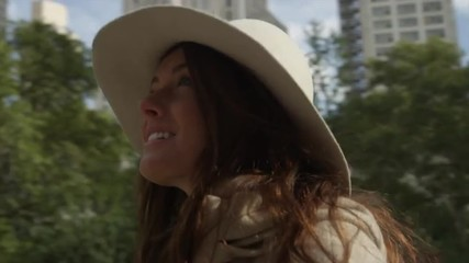 Close up tracking shot of smiling young woman looking up at trees and highrises / New York City, New York, United States