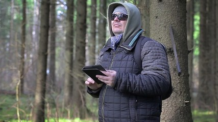 Hiker with machete, backpack and tablet PC in woods