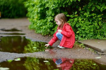 Adorable girl playing in a puddle on rainy day