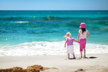 Two little sisters having fun on a sandy beach