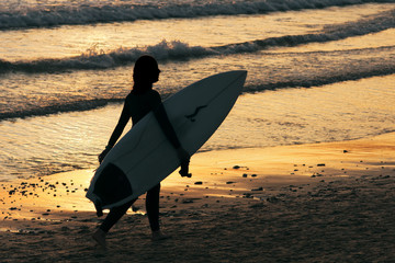 girl surfer on seashore at sunset in Doninhos beach Galicia