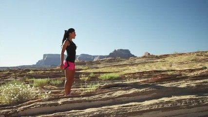 WS DS Young woman stretching in desert landscape / Lake Powell, Utah, USA