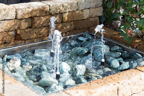 Leinwanddruck Bild splashing between the stones