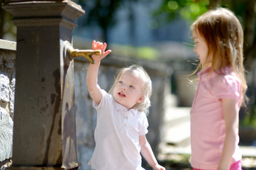 Two sisters having fun with water fountain