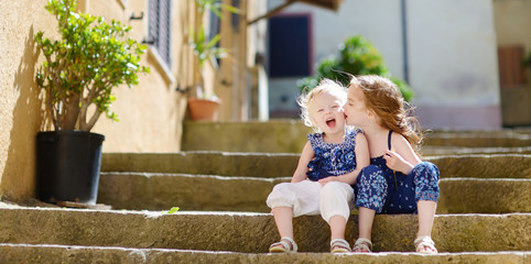 Two kid sisters sitting on stairs in italian town