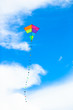 Leinwandbild Motiv Colorful kite flying in the wind background blue sky