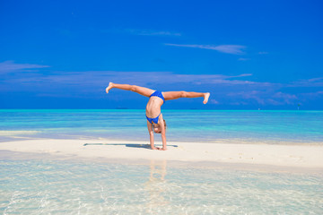 Adorable little girl having fun making cartwheel on tropical