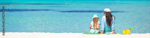canvas print picture Little girl and young mom relaxing at beach