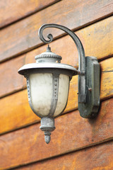 Close up vintage wall lamp wooden background.
