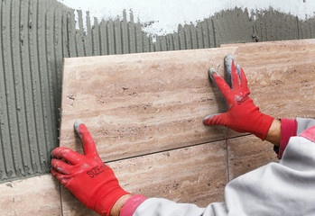 Ceramic Tiles. Tiler placing ceramic wall tile in position