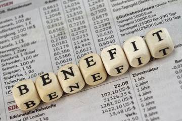 Benefit word built with letter cubes on newspaper background