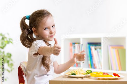 child eats healthy food showing thumb up - 82354563