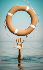 Hand in sea water with lifebuoy asking for help